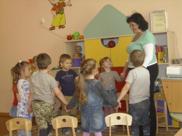 Дети и педагог стоят в кругу, держась за руки