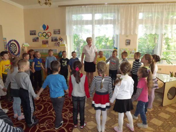 Дети и воспитатель стоят в кругу, держась за руки
