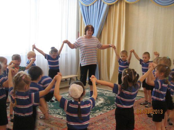Дети и воспитатель стоят в кругу, держась за руки и подняв их вверх