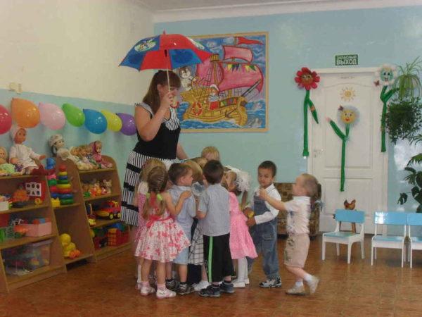 Воспитатель держит в руке яркий зонт, дети стоят рядом