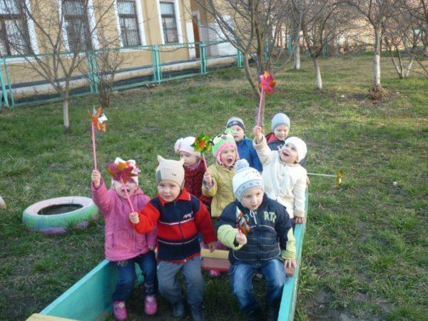 Дети на улице с вертушками в руках