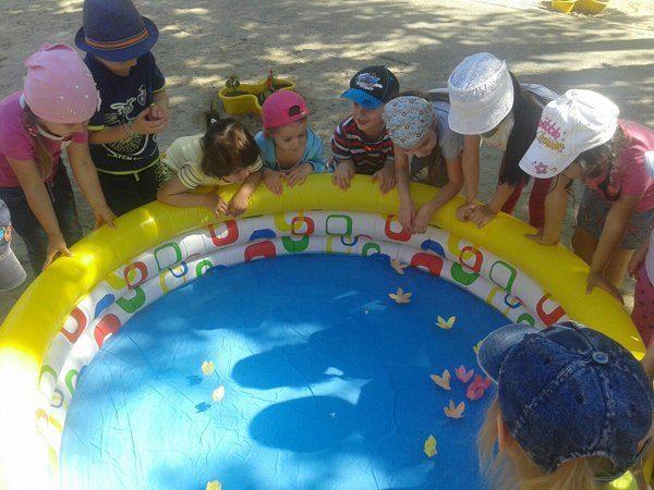 Дети рассматривают плавающие цветочки в надувном бассейне