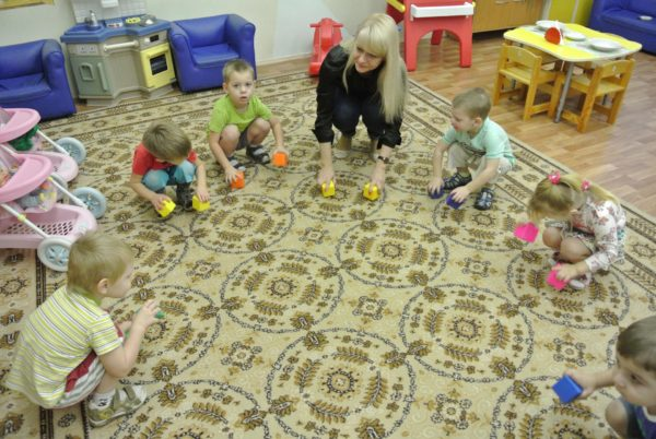 Дети с воспитательницей в кругу на ковре передвигают по полу кубики