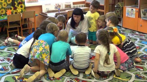 Дети сгруппировались вокруг воспитательницы на коврике