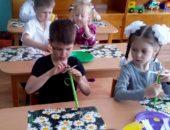 Дети, сидя за партами, делают поделки из бумаги