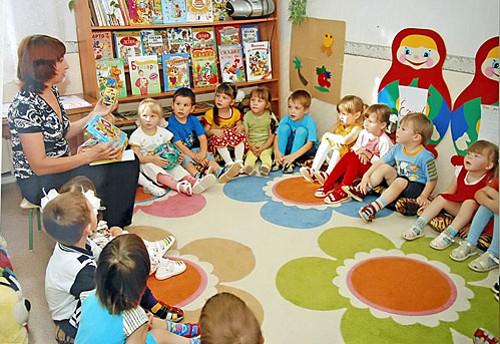 Дети сидят на подушечках на ковре и слушают воспитателя