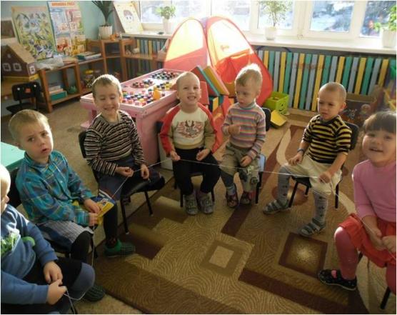 Дети сидят по кругу, держат ниточку