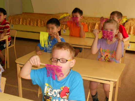 Дети сидят за столами и дуют на розовые и жёлтые флажки, на переднем плане мальчик в голубой футболке с Angry Birds