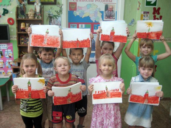 Дети стоят, держа в руках рисунки с изображениями Кремля