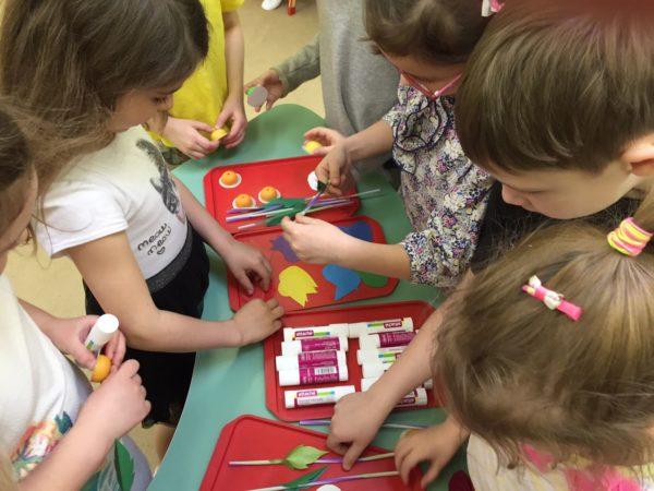 Дети стоят около стола с различными материалами для изготовления поделок