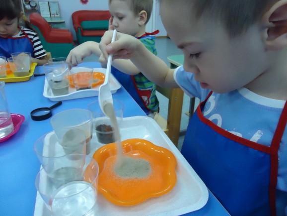 Дети в фартуках насыпают ложкой песок в оранжевую миску, стоящую на подносе