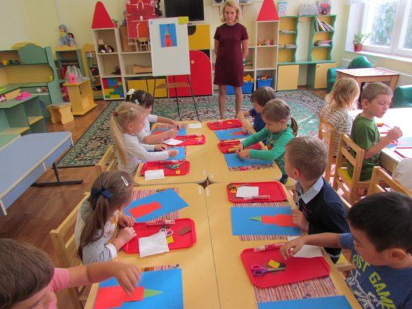 Дети выполняют аппликацию из цветной бумаги