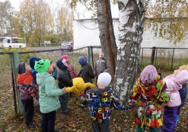 Дети, взявшись за руки, стоят вокруг дерева