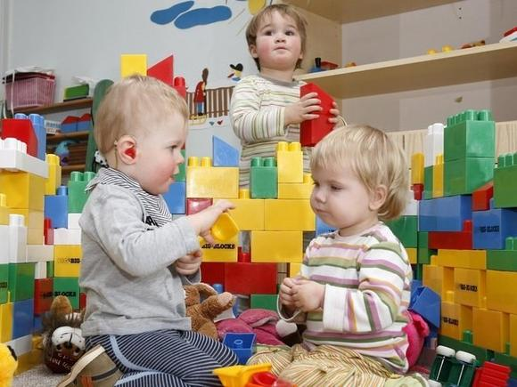 Трое детей ясельной группы играют на фоне построек из крупного конструктора
