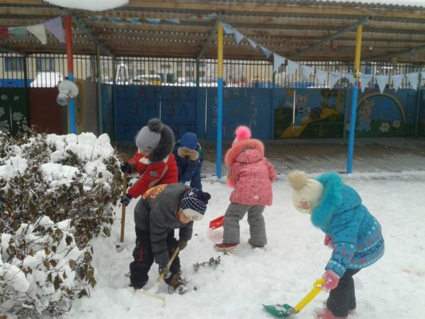 Дети сгребают лопатками снег на участке