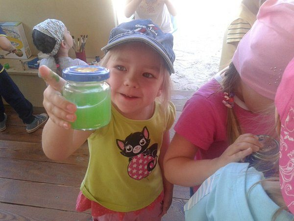 Девочка держит в руке баночку с зелёной жидкостью