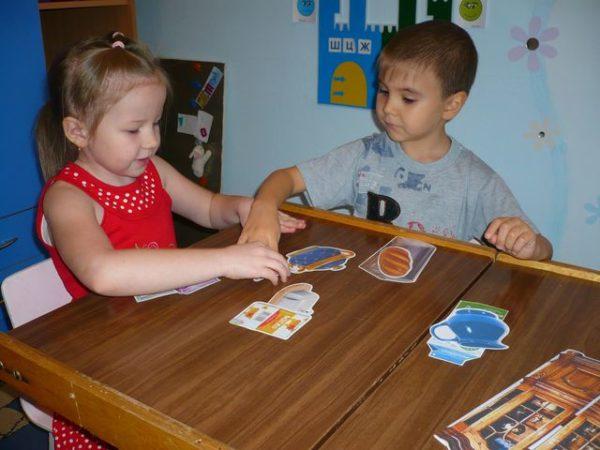 Девочка и мальчик раскладывают картинки с продуктами и посудой