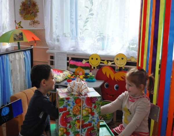 Девочка и мальчик жмут руки через коробку с большим бантом
