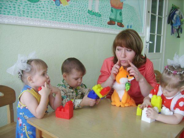 Девочка и воспитательница надавливают пальцами на щёки, вторая девочка и мальчик играют конструктором