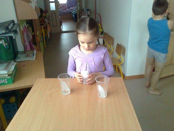 Девочка наблюдает за состоянием кусочков льда в пластиковых стаканах