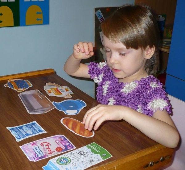 Девочка сортирует картинки с продуктами и посудой