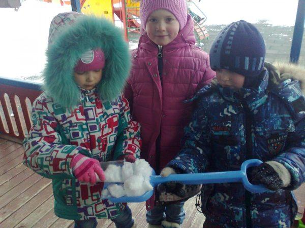 Девочка стаканом набирает снег с синей лопаты, которую держит мальчик