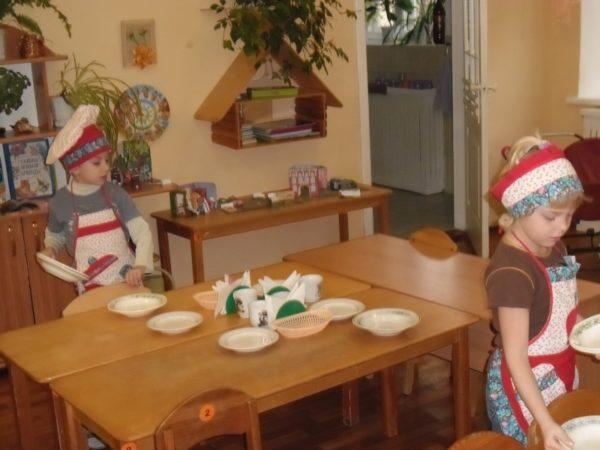 Двое детей накрывают на стол в детском саду