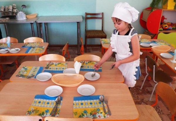 Девочка дежурит в столовой