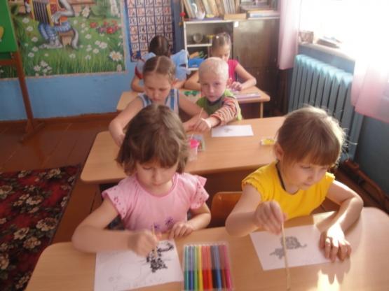 Дошкольники, сидя за партами, рисуют котёнка