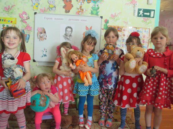 Девочки с игрушками в руках участвуют в досуге, посвященном А. Барто