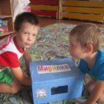 Два мальчика запустили руки в коробку-мирилку