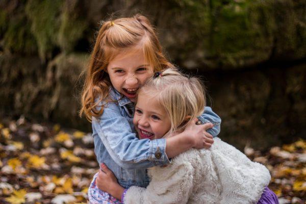 Две девочки обнимаются на фоне опавшей листвы