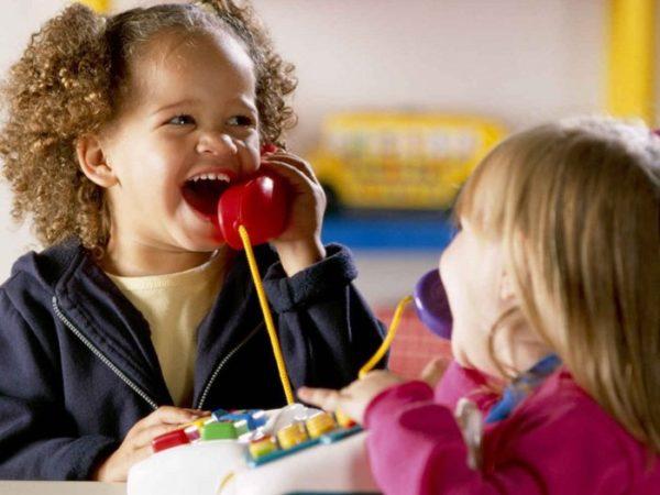 Две девочки с телефонными трубками в руках смеются