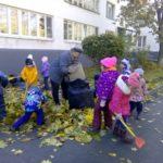 Дворник убирает листья в мешки