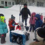 Дворник в окружении детей работает зимой