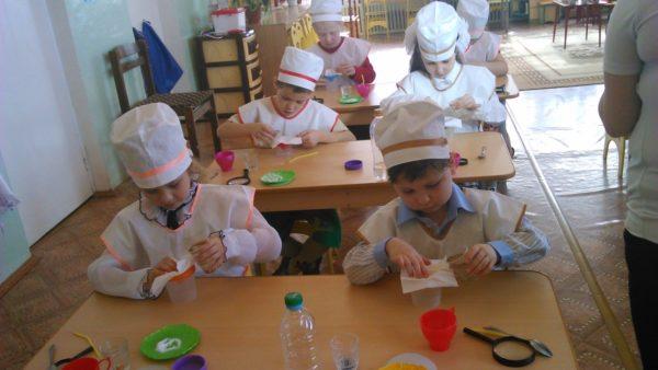Дети, сидя за партами, проводят эксперимент по очистке воды