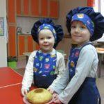 Две девочки держат в руках тарелку с испечённым караваем