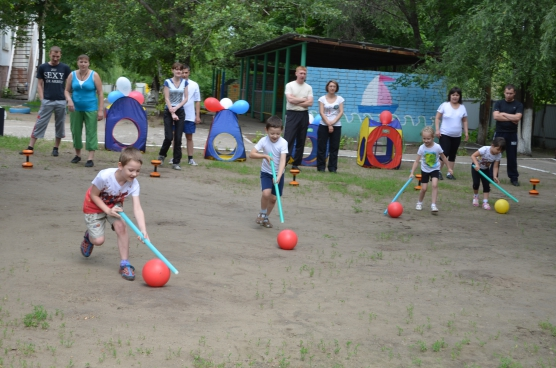 Дети на площадке участвуют в летнем спортивном мероприятии, родители наблюдают