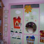 Логопедический уголок: на стене круглое зеркало, над ним — мягкая игрушка-солнце, справа и снизу — рисунки сказочных замков