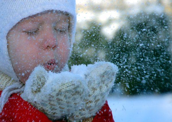 Мальчик дует на снег