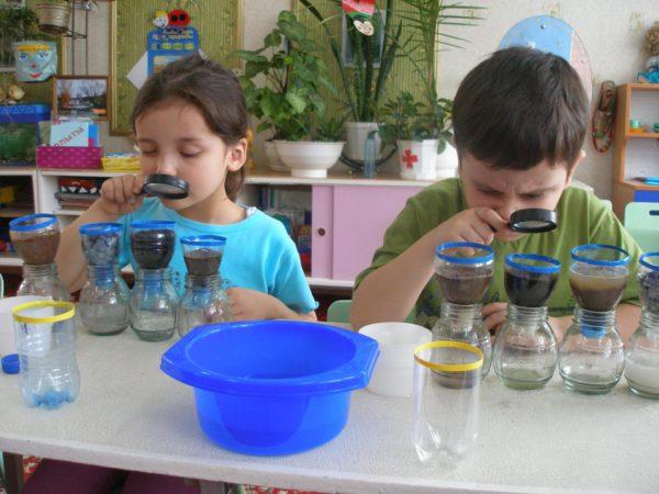 Мальчик и девочка рассматривают через лупу образцы почв