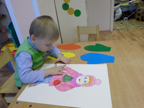 Мальчик подбирает одежду нарисованной кукле