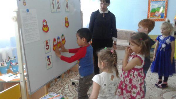 Мальчик размещает бумажных матрёшек на доске, остальные дети и воспитатель стоят рядом