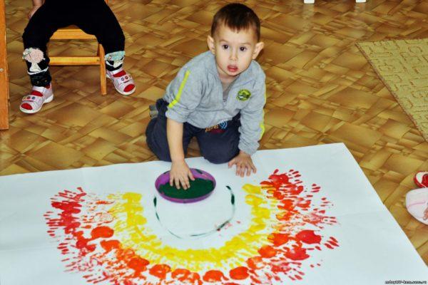 Мальчик рисует ладошками