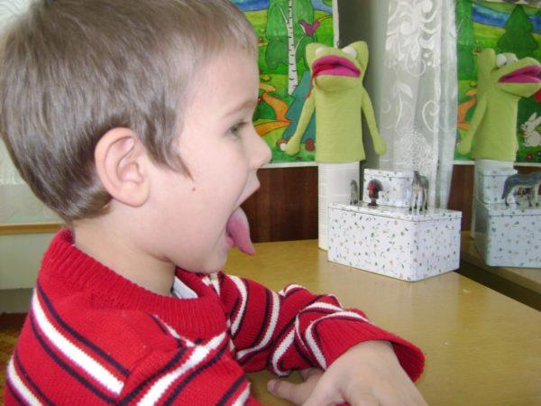 Мальчик в красном свитере с белыми и чёрными полосками высунул язык