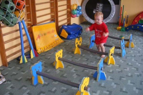 Мальчик в красной футболке бежит через жёлто-голубые препятствия в спортивном зале ДОУ
