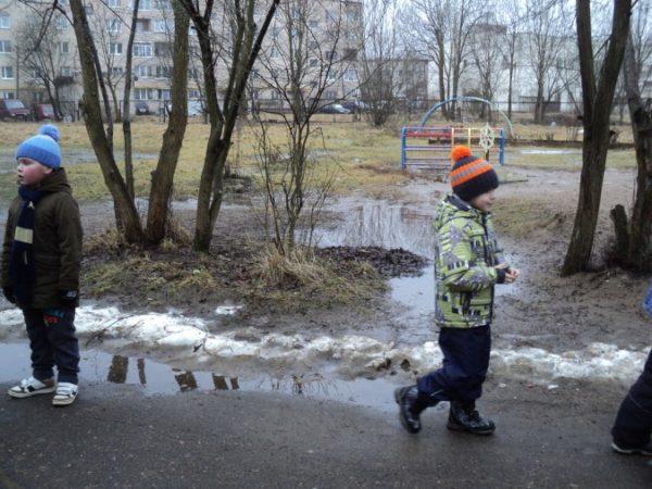 Мальчики ходят по дороге, наблюдая за таянием снега