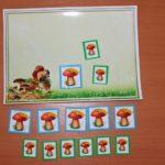 На картинке, лежащей на столе, белочка и три гриба в прямоугольниках, под картинкой на карточках пять больших и шесть маленьких грибов