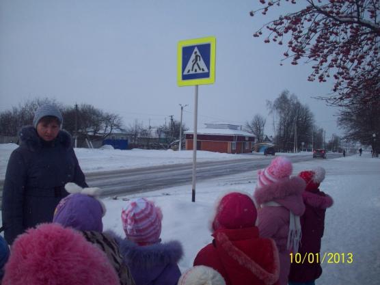 Дети и воспитатель наблюдают за пешеходным переходом и проезжей частью