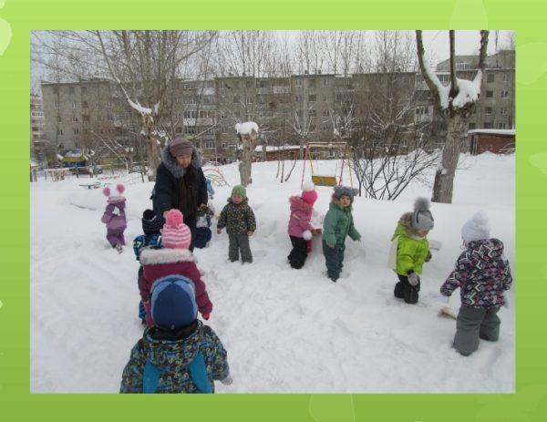 Дети и воспитатель на заснеженном участке